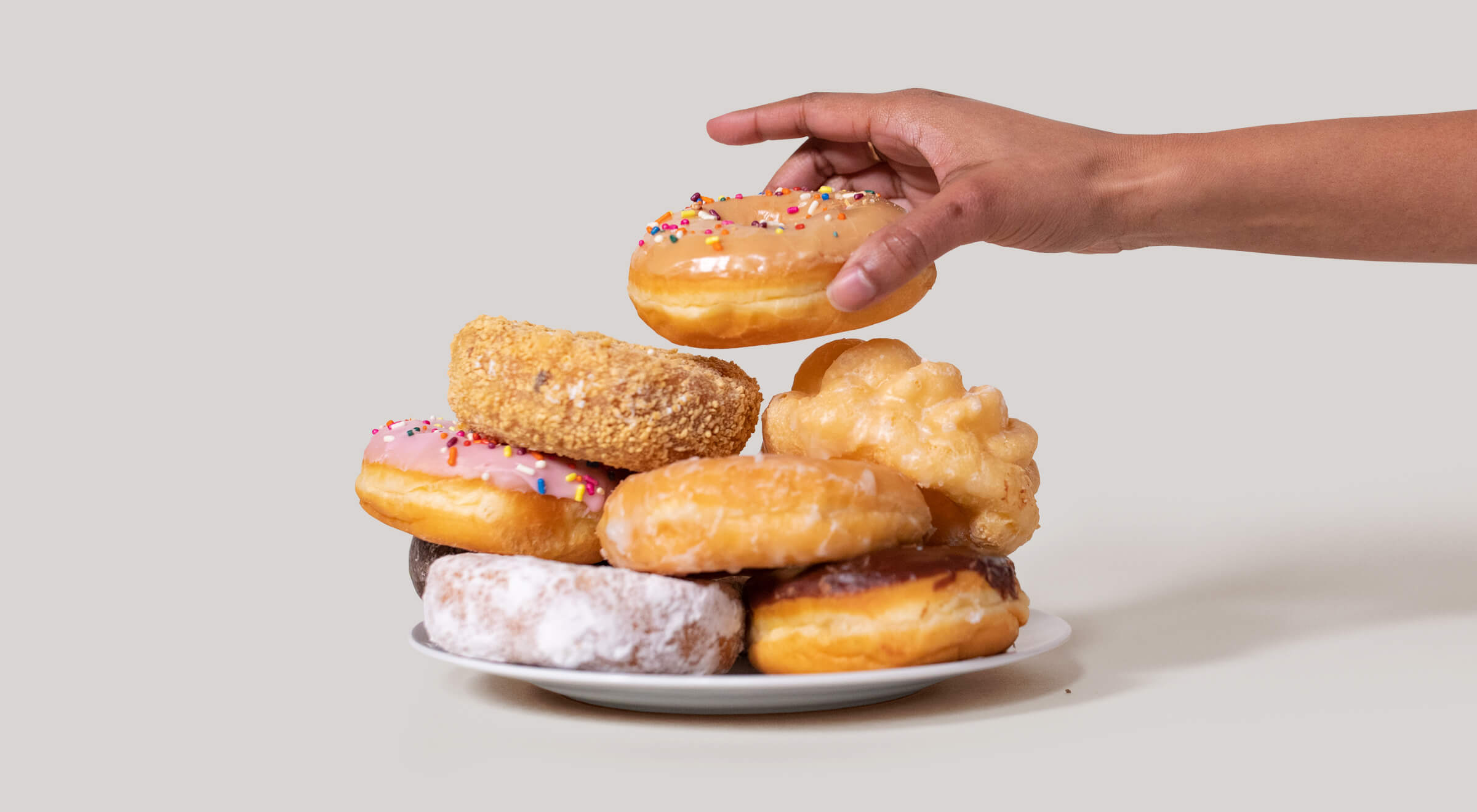 Hand reaching for a pile of assorted donuts